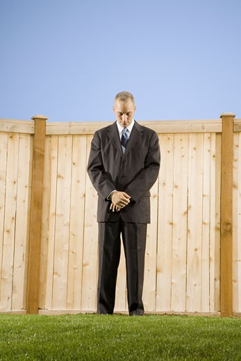 Low angle view of a businessman standing in front of a wall looking down : Stock Photo
