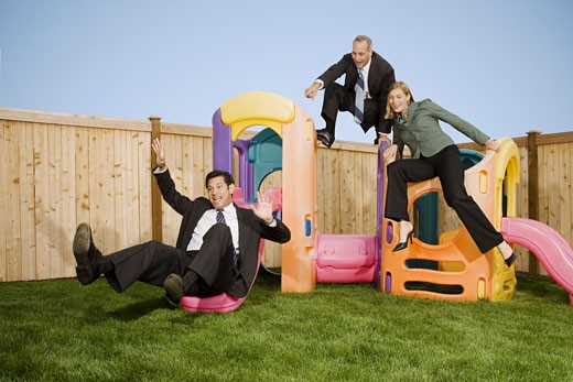 Two businessmen and a businesswoman playing with jungle gym : Stock Photo