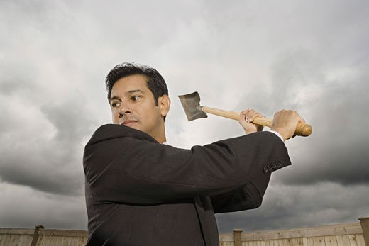 Low angle view of a businessman swinging a shovel : Stock Photo
