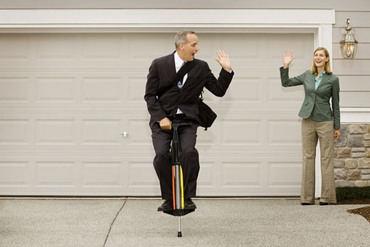 Stock Photo: 1660R-4637 Businessman on a pogo stick waving at a businesswoman