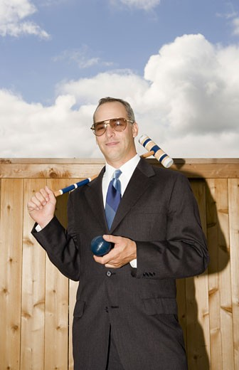 Businessman and a businesswoman playing croquet : Stock Photo