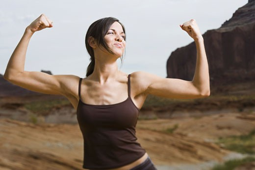 Young woman flexing her muscles : Stock Photo