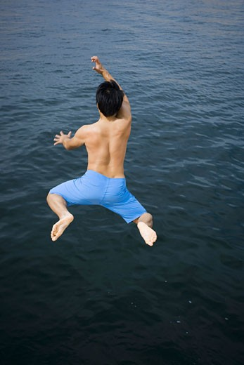 Rear view of a young man jumping in a lake : Stock Photo