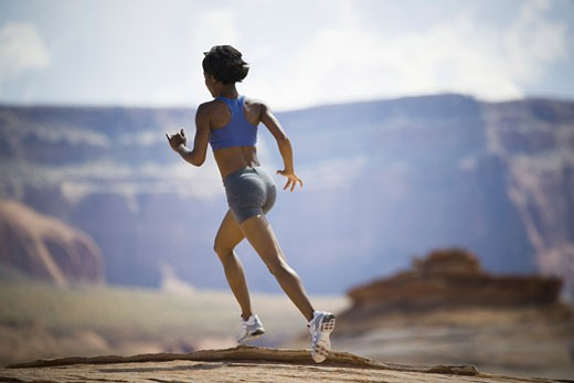 Rear view of a young woman jogging : Stock Photo