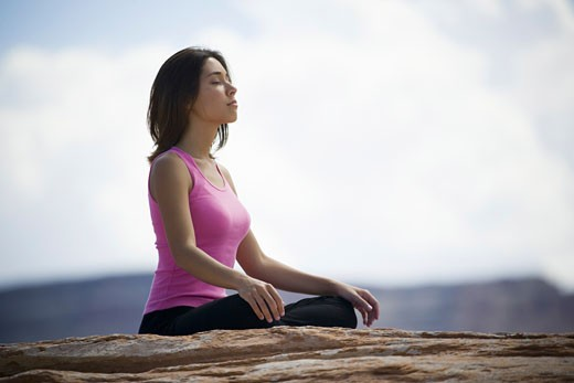 Profile of a young woman meditating : Stock Photo
