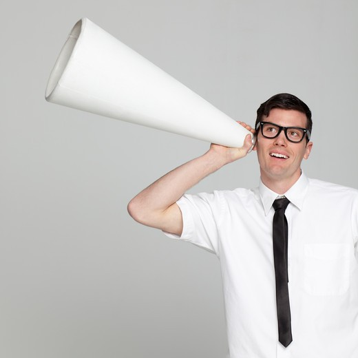 Studio portrait of young man with megaphone : Stock Photo