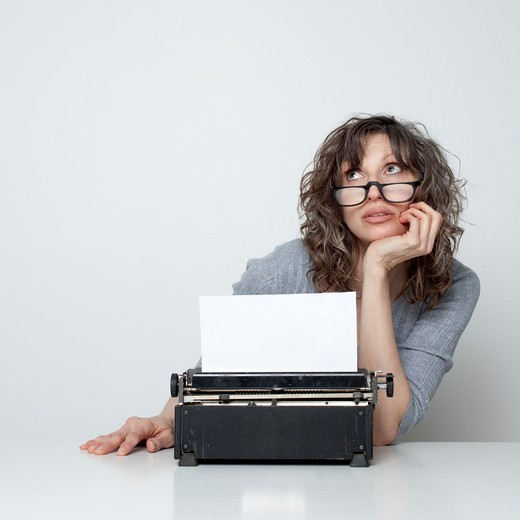 Stock Photo: 1660R-49333 Studio shot of bored woman sitting at table with typewriter