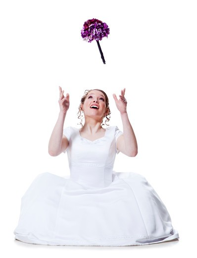 Stock Photo: 1660R-49529 Happy bride throwing bouquet, studio shot