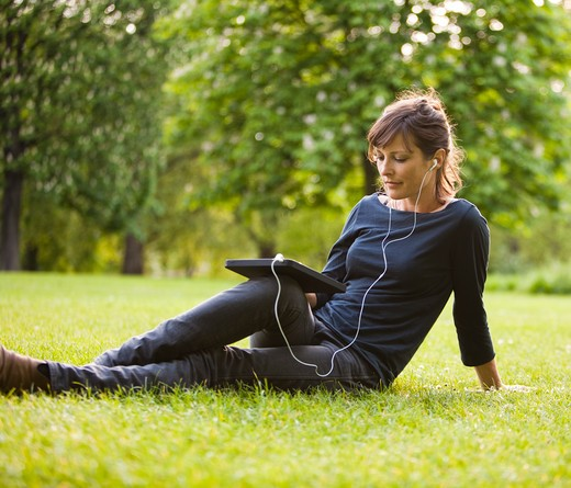 UK, London, Young woman sitting in park and using digital tablet : Stock Photo