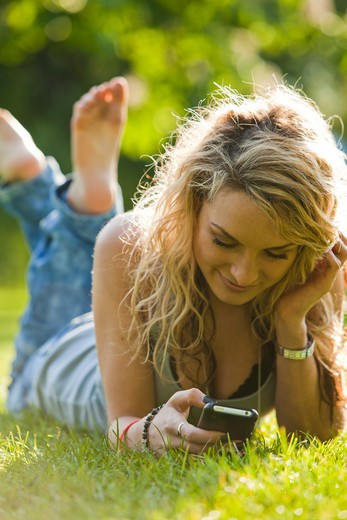 Stock Photo: 1660R-49552 UK, London, Young woman lying in park and using mobile phone