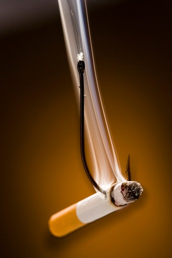 Cigarette with a fish hook through it : Stock Photo