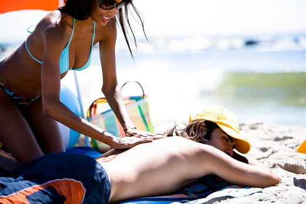 Stock Photo: 1660R-51444 Woman applying sun screen to man