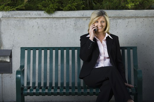 Businesswoman on cellular sitting on a bench : Stock Photo