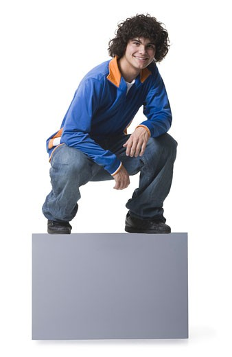 Portrait of a teenage boy crouching and smiling : Stock Photo