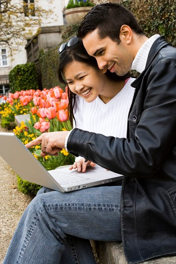 Couple using a laptop : Stock Photo