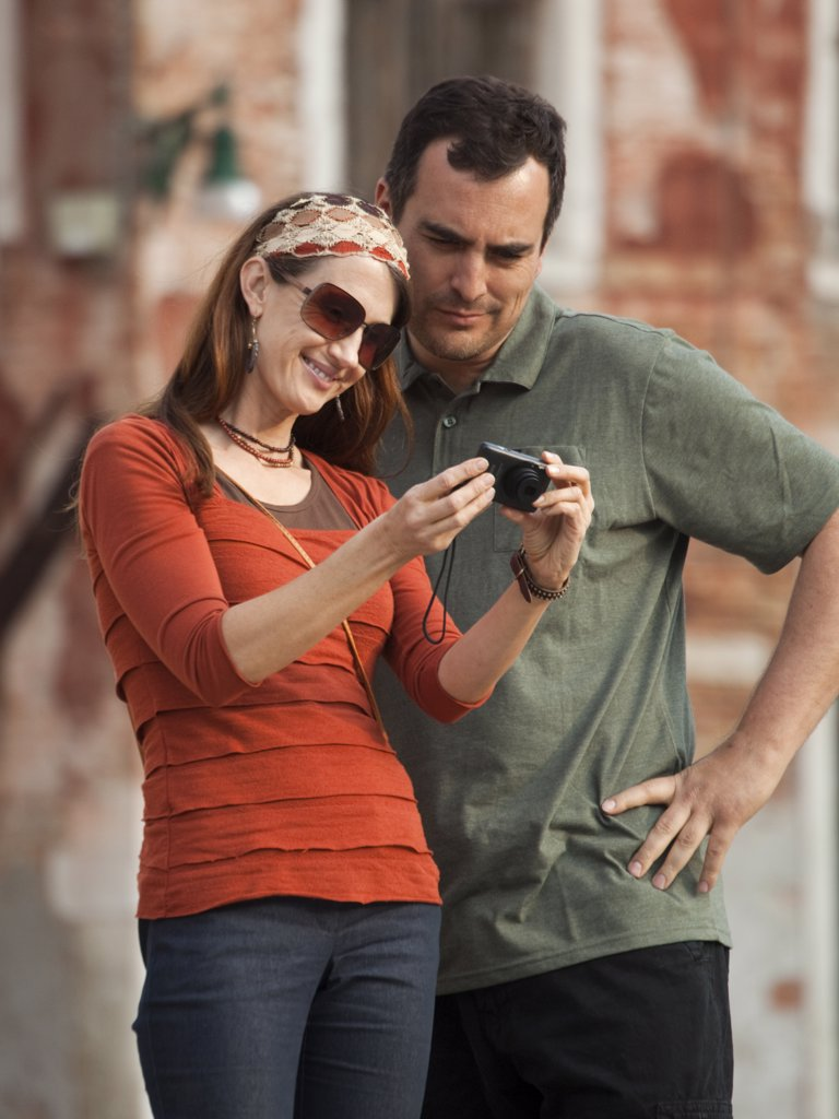 Stock Photo: 1660R-52764 Italy, Venice, Couple viewing digital camera in city