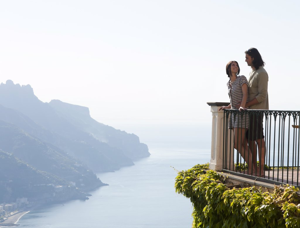 Stock Photo: 1660R-52906 Italy, Ravello, Young couple standing together at balustrade