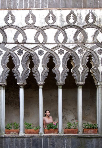 Italy, Ravello, Woman standing on balcony between ornate columns : Stock Photo