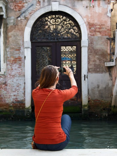 Italy, Venice, Mature woman posing by historic canal : Stock Photo
