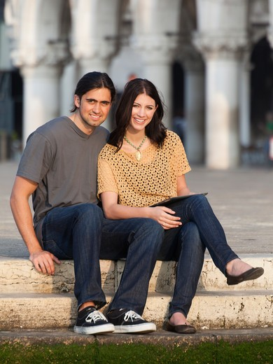 Stock Photo: 1660R-53185 Italy, Venice, Portrait of young couple sitting on steps on St. Mark's Square