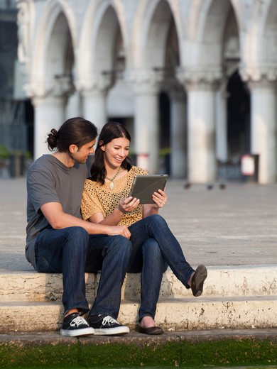 Stock Photo: 1660R-53186 Italy, Venice, Young couple using digital tablet on St. Mark's Square