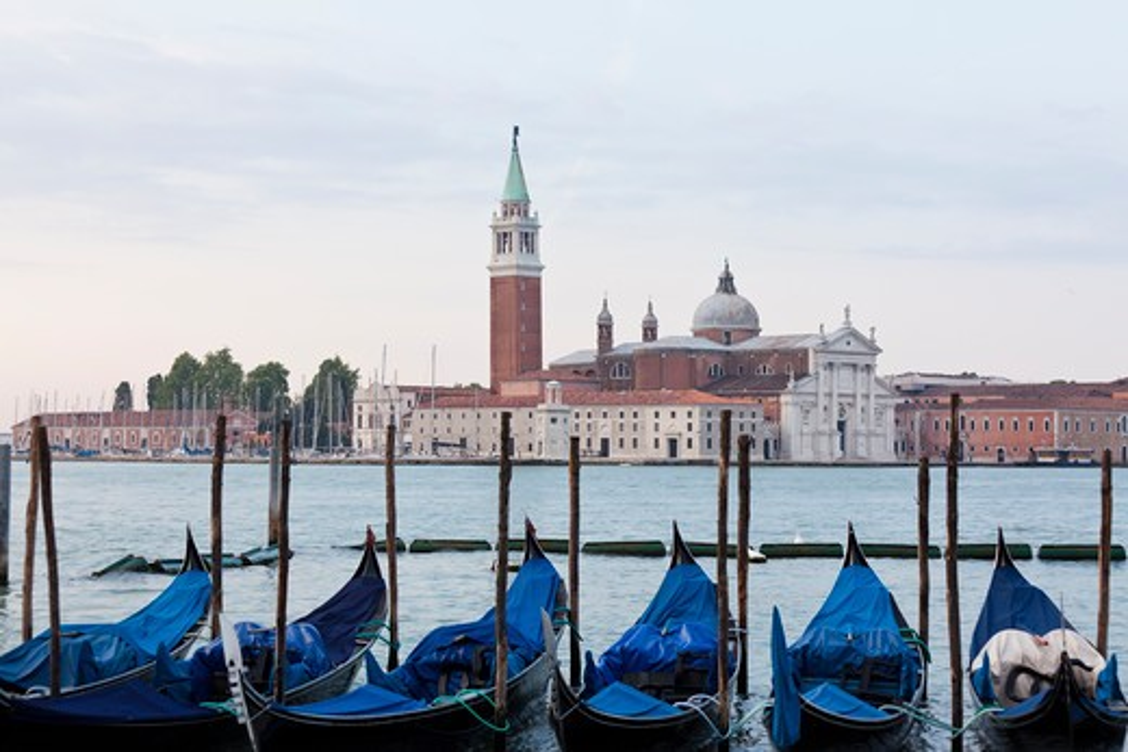 Stock Photo: 1660R-53197 Italy, Venice, Young couple embracing by lagoon, gondolas and San Giorgio Maggiore church in background