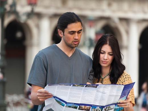 Stock Photo: 1660R-53202 Italy, Venice, Young couple looking at map on St. Mark's Square