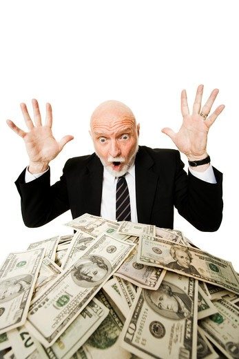 Closeup of businessman looking at pile of money : Stock Photo