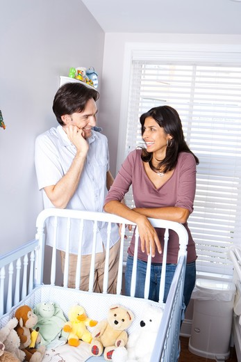 Stock Photo: 1660R-54558 Married couple leaning on baby crib