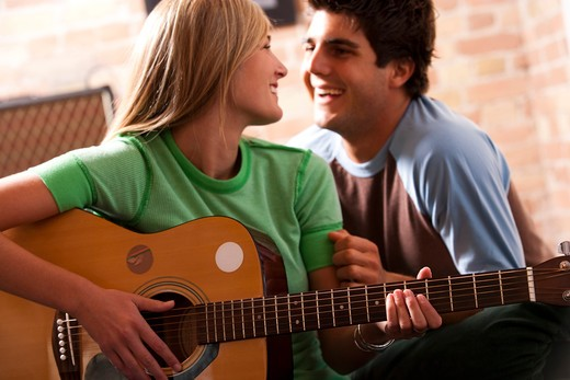 Woman playing guitar with man watching : Stock Photo