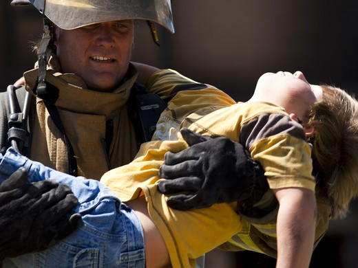 Fire fighter rescuing child : Stock Photo