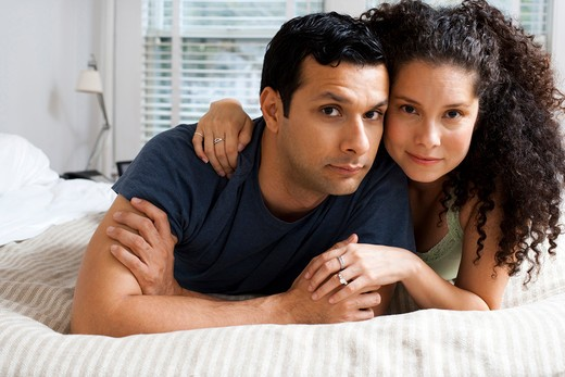 Stock Photo: 1660R-55846 Man and woman on bed snuggling