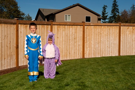 Girl and boy in yard in halloween costumes : Stock Photo