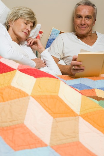 Mature man in bed reading with sleeping woman : Stock Photo