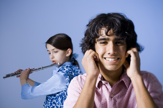 Girl playing the flute with her brother not listening : Stock Photo