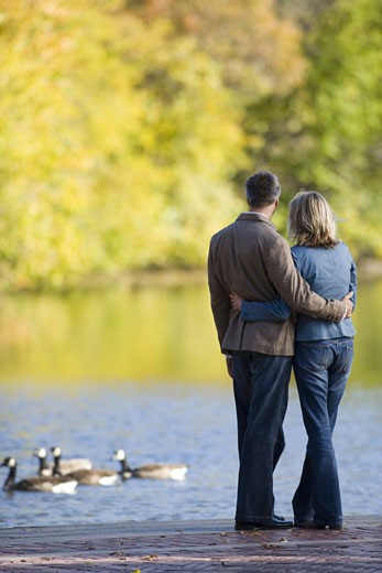Stock Photo: 1660R-5680 Rear view of a woman and man by a lake