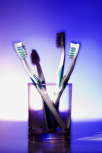 Close-up of four toothbrushes in a glass : Stock Photo
