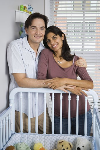 Portrait of a couple leaning on a crib : Stock Photo