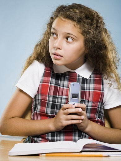 Stock Photo: 1660R-57970 Girl sitting at desk with workbook hiding cell phone