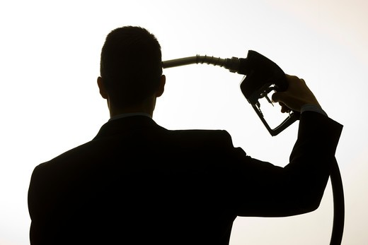 man holding a gas pump to his head : Stock Photo