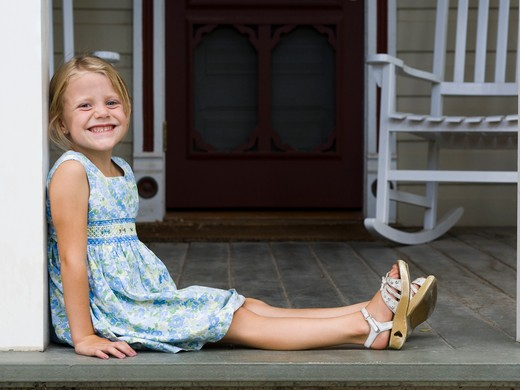 Stock Photo: 1660R-58793 girl sitting on the front porch