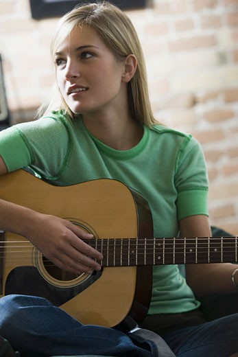 Stock Photo: 1660R-5880 Close-up of a teenage girl playing the guitar