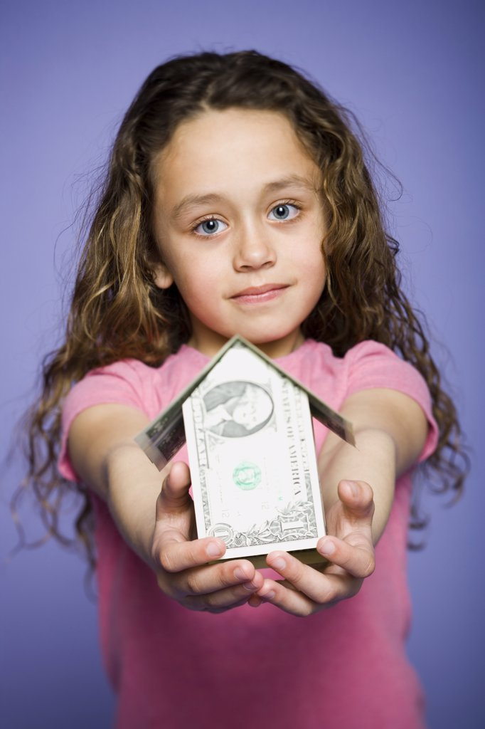 Young girl with a little house made of banknotes : Stock Photo