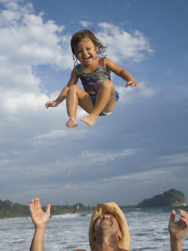 Father tossing his daughter in air : Stock Photo