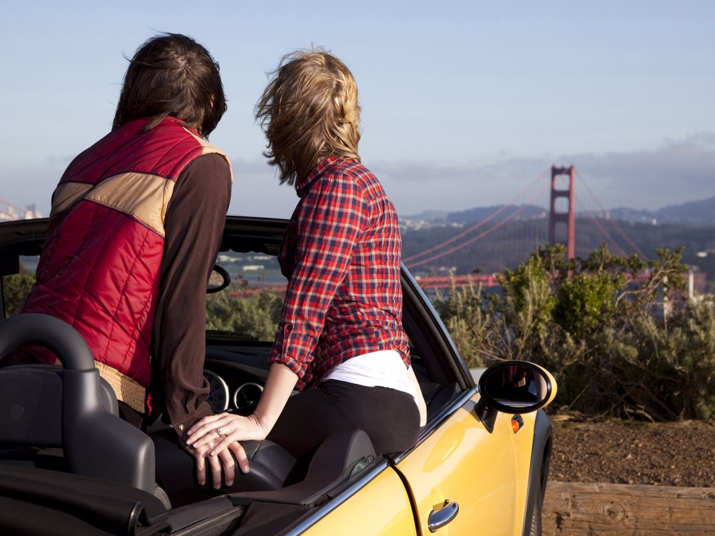 Stock Photo: 1660R-59290 USA, San Francisco, California, young couple sitting in convertible car and looking at Golden Gate Bridge in distance