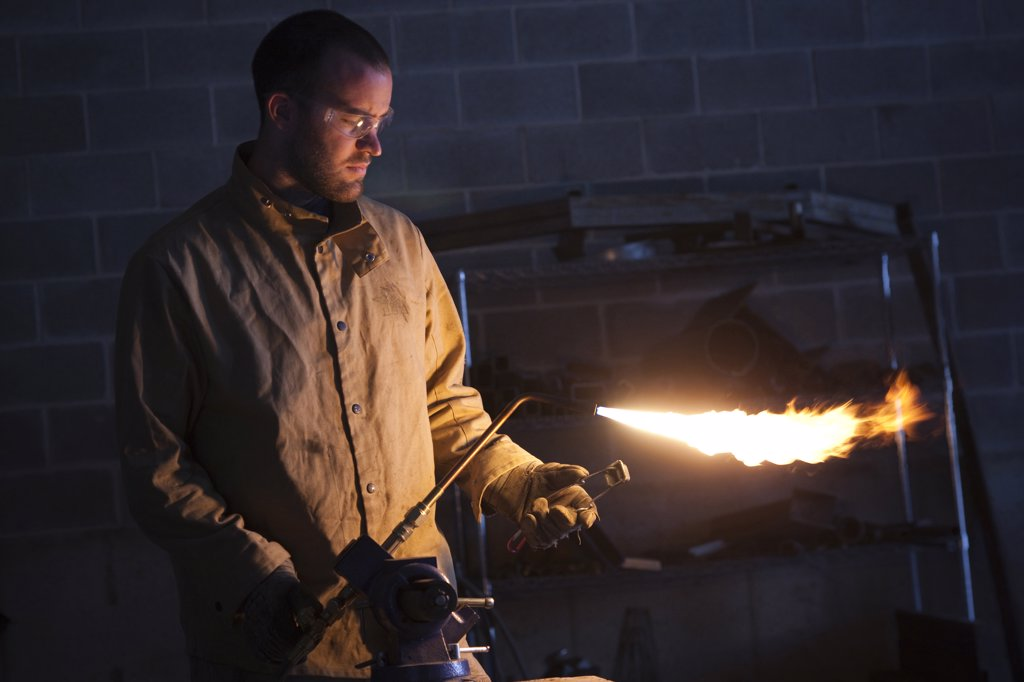 USA, Utah, Orem, male welder using blowtorch in workshop : Stock Photo