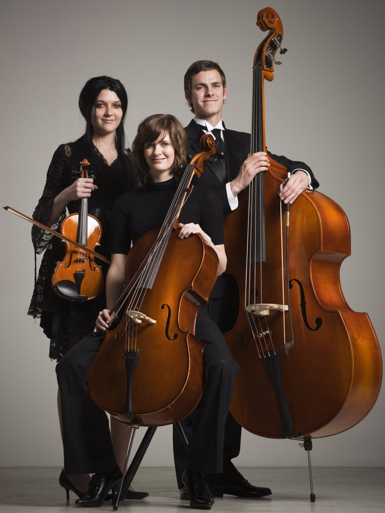 Studio portrait of three young musicians with instruments : Stock Photo