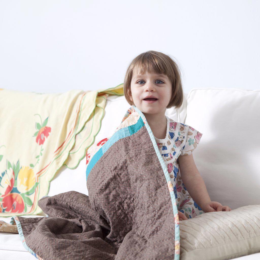 Stock Photo: 1660R-59654 USA, California, San Francisco, girl (2-3) sitting on sofa covered with blanket