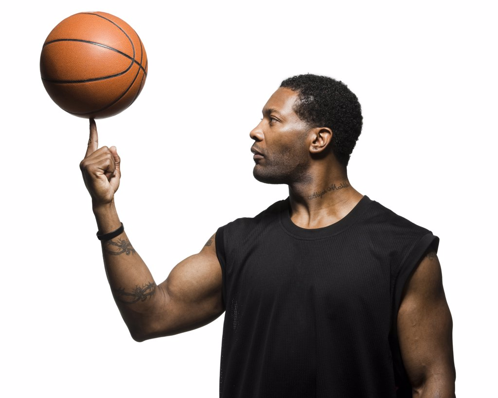 Stock Photo: 1660R-60016 Mid adult man spinning basketball in air