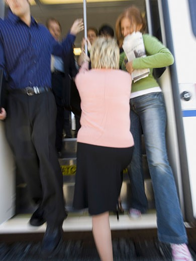 Stock Photo: 1660R-6036 People exiting a passenger train while a woman tries to enter the train